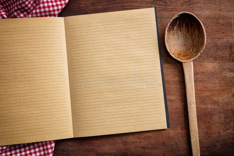 Taccuino, siviera della cucina e tovaglia rossa sulla tavola di legno, vista superiore, spazio della copia fotografie stock libere da diritti