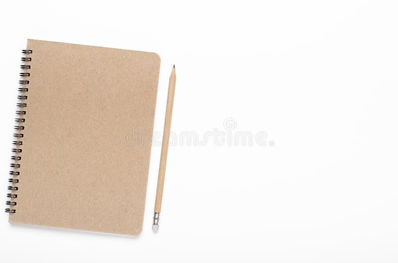 Taccuino su una coclea della carta kraft con una matita su un fondo bianco Scrivania, cancelleria Copi lo spazio, la vista superi fotografia stock