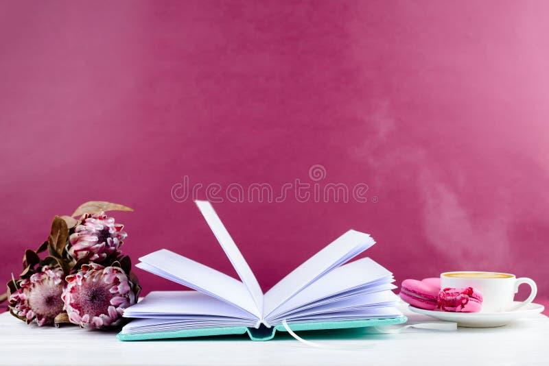 Taccuino, tazza di caffè e tulipani vicini su fondo rosa con immagini stock