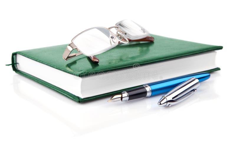 Taccuino verde con la penna isolata su bianco immagini stock libere da diritti