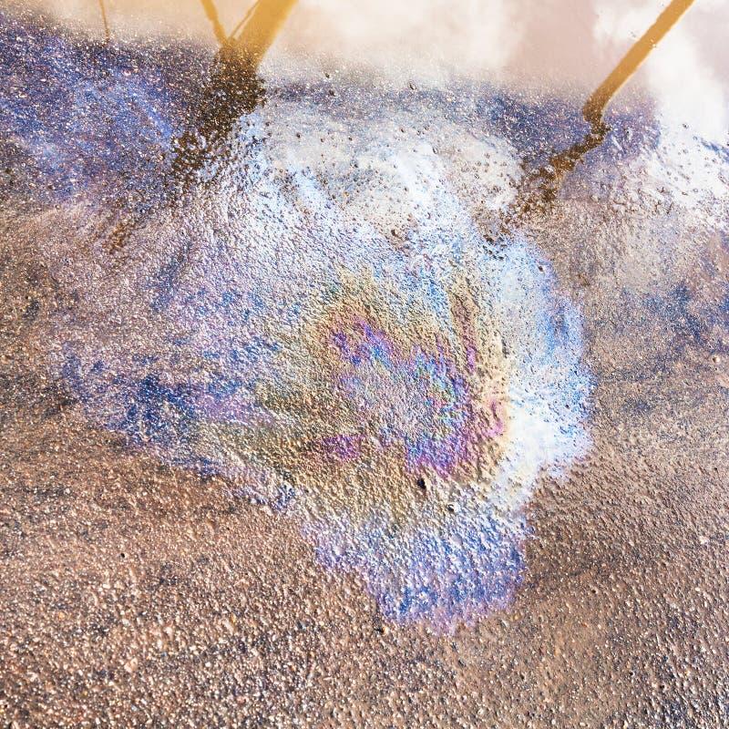 Tache d'arc-en-ciel d'huile de moteur sur le trottoir humide d'asphalte photographie stock