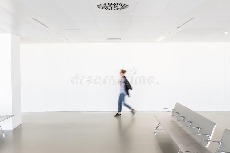 Tache floue de mouvement de femme marchant au couloir vide blanc contemporain photo stock