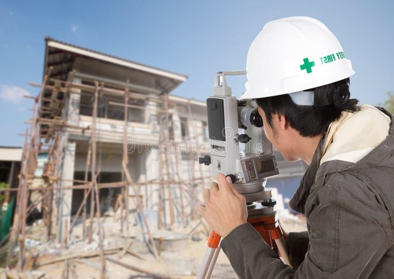 Tacheometer ou théodolite d'utilisation d'ingénieurs avec la construction de maison image stock