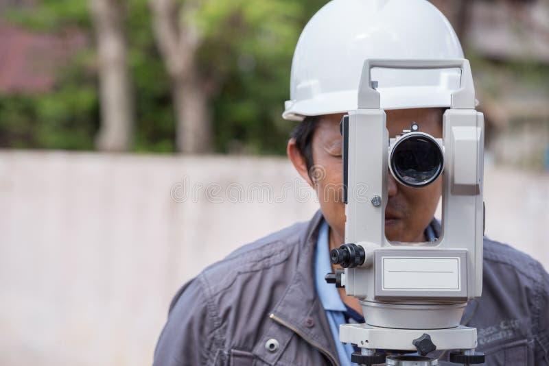 Tacheometer ou théodolite d'utilisation d'ingénieurs pour la ligne colonnes d'enquête photographie stock libre de droits