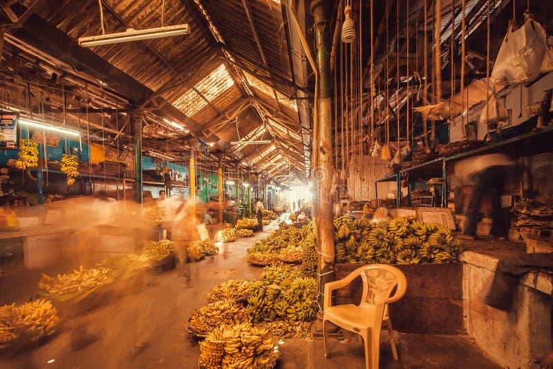 Taches floues de mouvement des clients de marche dans l'entrepôt foncé avec des bananes et des fruits photographie stock libre de droits