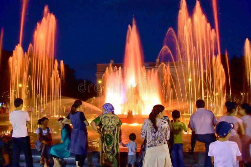 TACHKENT, UZBEKISTÁN - 23 DE MAYO DE 2011: Gente del Uzbek que recolecta por la tarde delante de una fuente del canto fotos de archivo