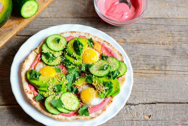 Taci sani con le uova di quaglia, le fette di avocado fresche, il cetriolo, i hummus della barbabietola ed il prezzemolo Taci rap fotografie stock