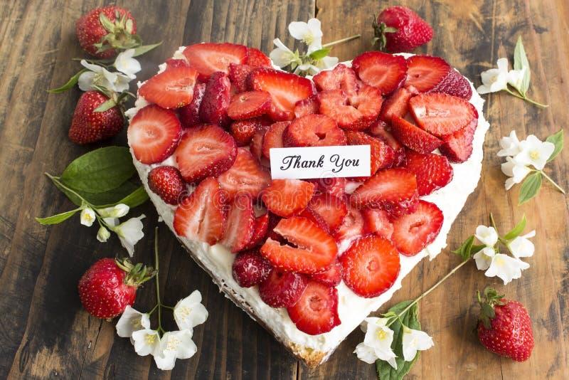 Tacka dig att card med hjärtaostkaka med jordgubbar royaltyfria foton