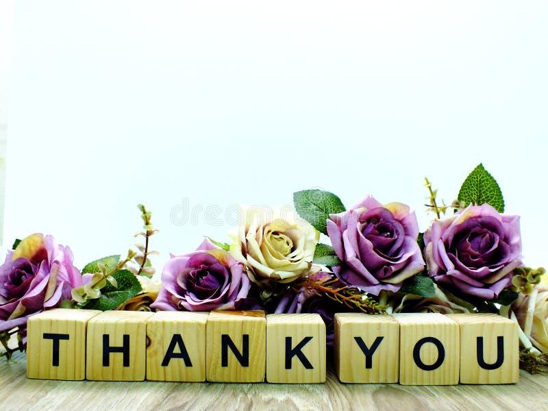 Tacka dig att uttrycka träkvarteret med den konstgjorda rosblommadekoren royaltyfri fotografi