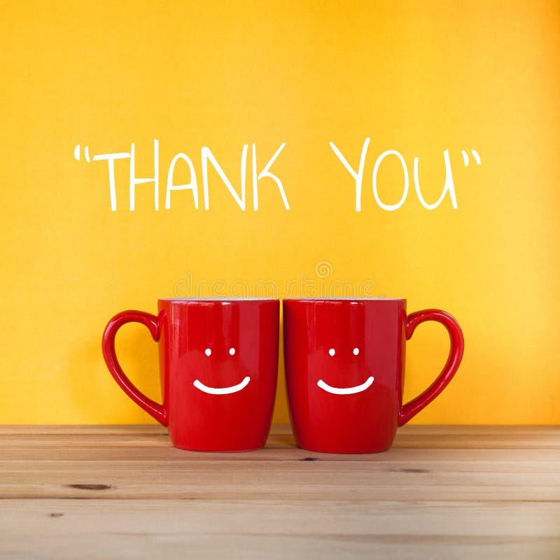 Tacka dig att uttrycka Två koppar kaffe och ställning tillsammans fotografering för bildbyråer