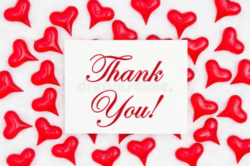 Tacka dig det hälsa kortet med röda hjärtor på vitt tyg royaltyfria bilder