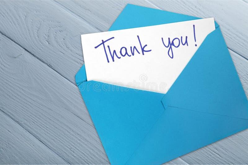 Tacka dig för att card och kuvertet på träbakgrund royaltyfri fotografi