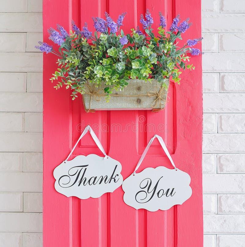 Tacka dig garneringbräden som hänger på rosa dörr royaltyfri bild
