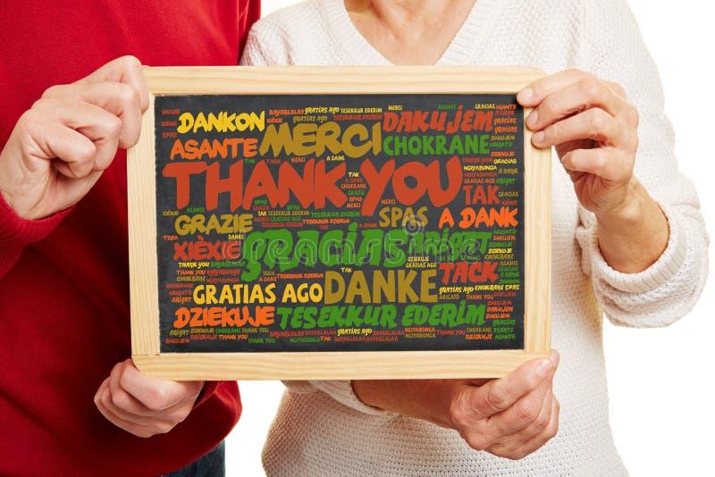 Tacka dig i många språk på svart tavla fotografering för bildbyråer