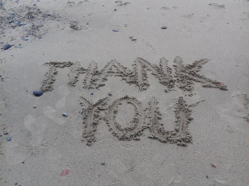 Tacka dig i sanden arkivbild
