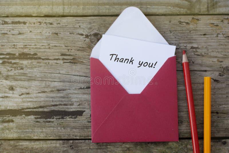 Tacka dig inskriften - rött kuvert med det tomma kortet på träbakgrund med kopieringsutrymme och röda blyertspennor royaltyfria bilder