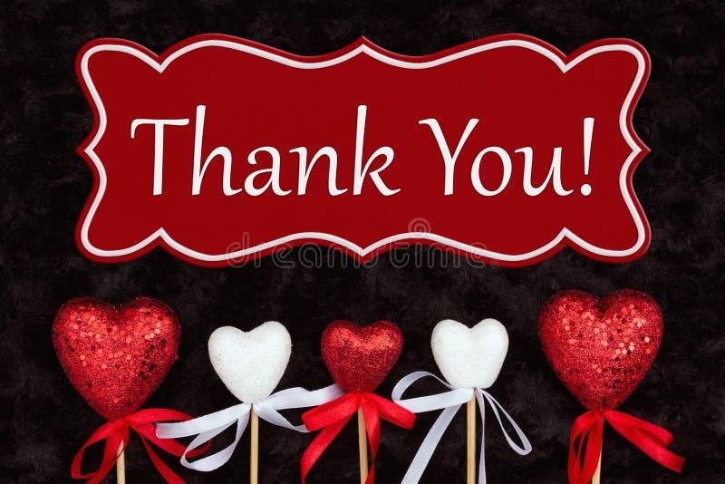 Tacka dig meddelandet med vita och röda hjärtor på svart arkivfoton