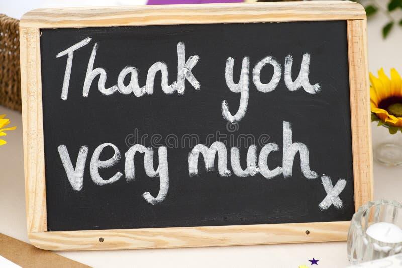Tacka dig mycket meddelande som är skriftligt i krita på en liten blackboa arkivbilder