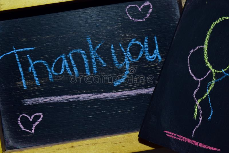 Tacka dig på färgrikt handskrivet för uttryck på svart tavla royaltyfria foton