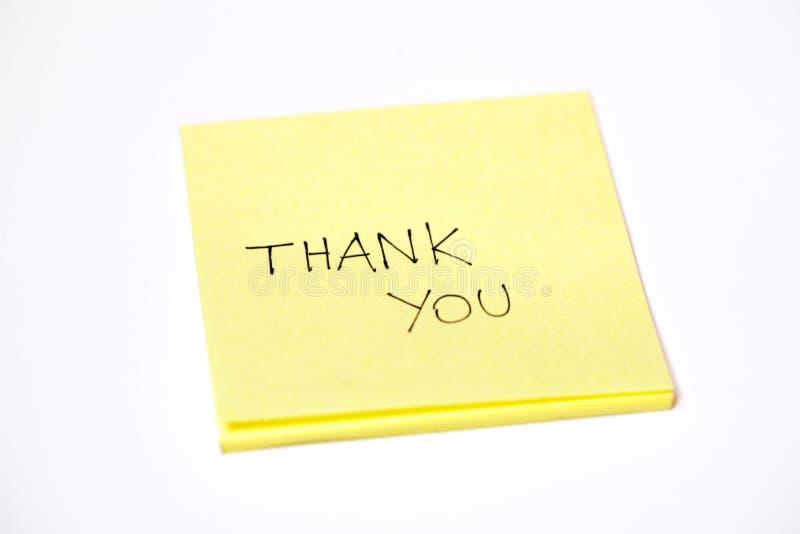 Tacka dig som är skriftlig på posta-honom, eller ett klibbigt noterar, isolerat på vit arkivfoto