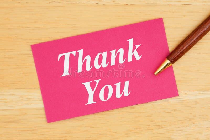 Tacka dig text på rosa kort med pennan royaltyfri bild