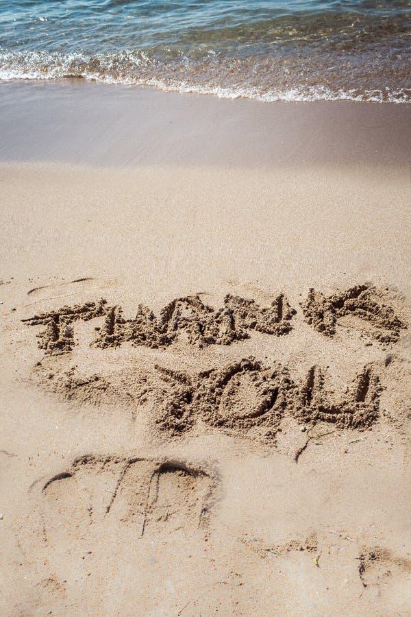 Tacka dig, text på sand på stranden royaltyfri foto