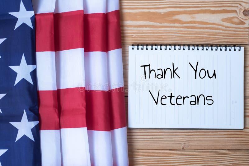 Tacka dig veterantext som är skriftlig i svart tavla med flaggan av Amerikas förenta stater på träbakgrund royaltyfria bilder