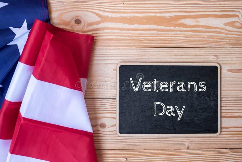 Tacka dig veterantext som är skriftlig i svart tavla med flaggan av Amerikas förenta stater på träbakgrund fotografering för bildbyråer