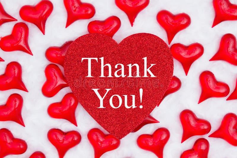 Tacka som dig, blänker meddelandet på hjärta med röda hjärtor på vitt tyg royaltyfria bilder