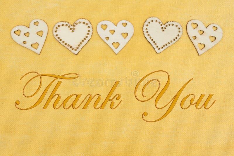 Tacka som dig, målade meddelandet med trähjärtor förestående bekymrad guld royaltyfri fotografi