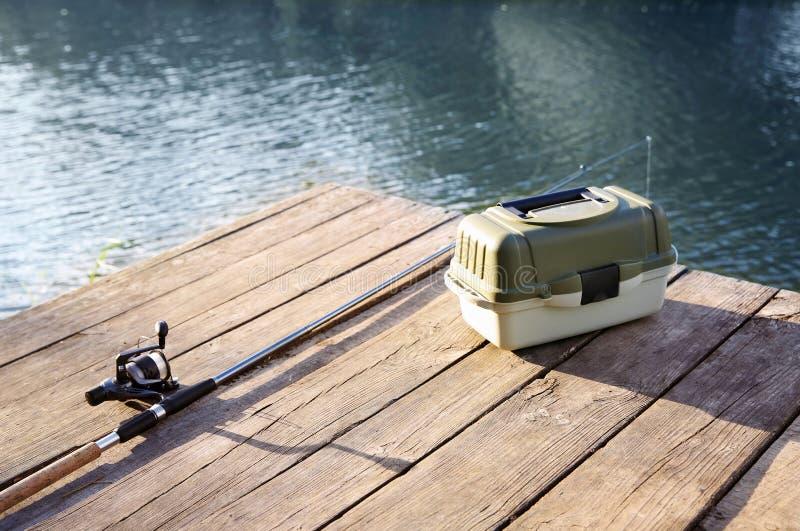 Tackla asken och stången för att fiska på träpir arkivfoton