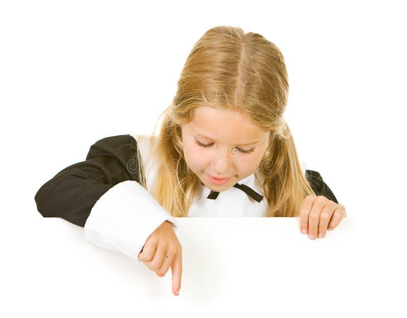 Tacksägelse: Flickan vallfärdar blickar ner på det vita kortet arkivfoton