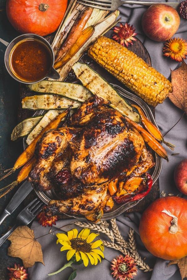 Tacksägelsedagen grillade hel välfylld höna, eller kalkon tjänade som med sås, havre och grönsaker på köksbordet som dekorerades  arkivfoto