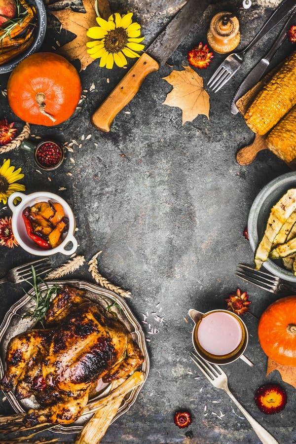 Tacksägelsematställeförberedelse Grillad hel höna eller kalkon, sås med grillade höstgrönsaker, havre, bestick, garnering arkivbild