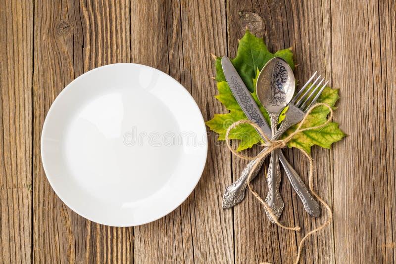 Tacksägelsematställeplatta med gaffeln, kniven och höstsidor på lantlig trätabellbakgrund Bästa sikt, kopieringsutrymme royaltyfria foton