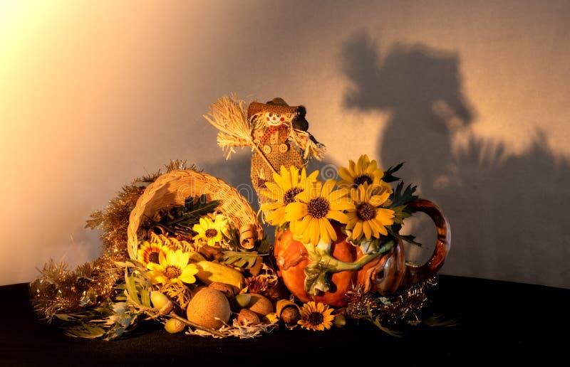 Tacksägelseymnighetshornhöjdpunkten med porslinpumpakannan, solrosor och fågelskrämman som firar nedgånghöst, skördar holid arkivfoto