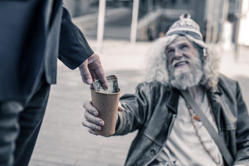 Tacksam hemlös man med smutsigt hår som sträcker den tomma kaffekoppen royaltyfri foto
