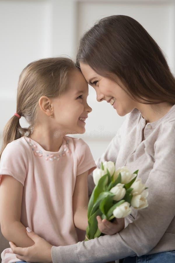 Tacksam moder och dotter som trycker på försiktigt pannor för att fira familjferie royaltyfria foton