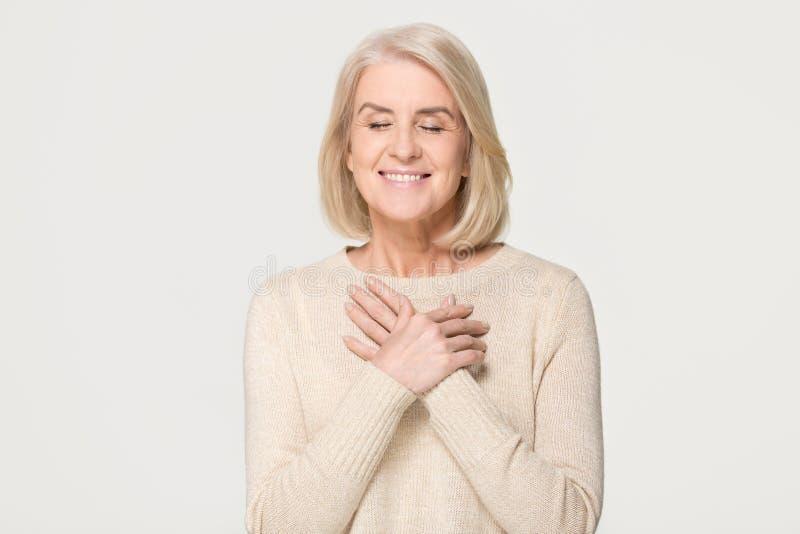 Tacksam mogen kvinna som rymmer händer på bröstkorgen som isoleras på bakgrund fotografering för bildbyråer