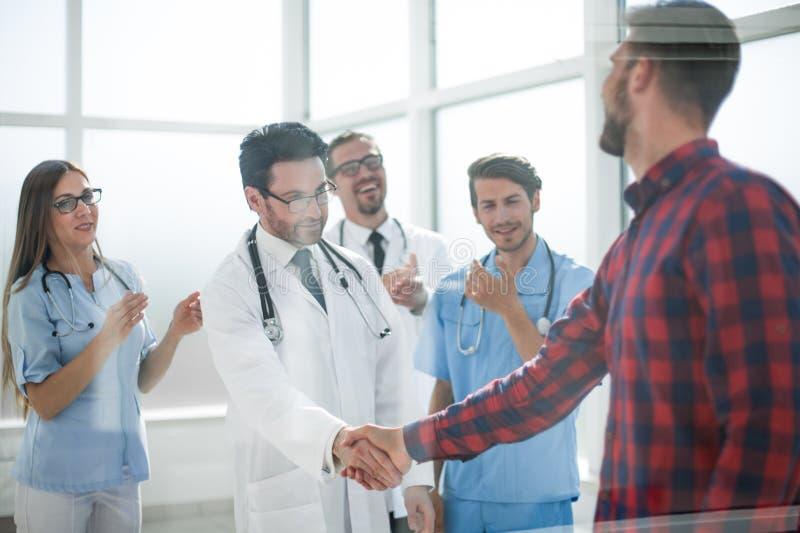 Tacksam patient som skakar doktorshanden fotografering för bildbyråer