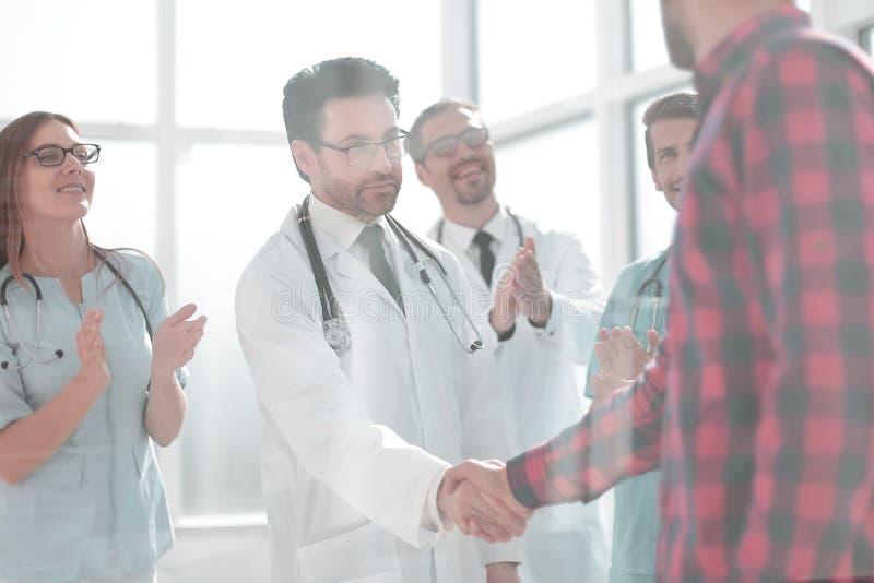 Tacksam patient som skakar doktorshanden arkivfoton