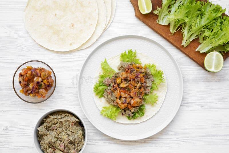 Taco fait maison de crevette avec des ingrédients, vue supérieure Fond en bois blanc Configuration plate, aérienne photographie stock