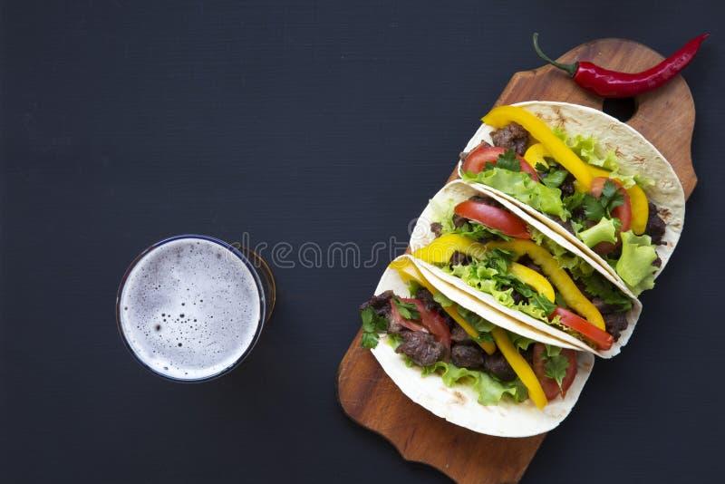 Taco's met bier op de raad op een zwarte houten achtergrond, bovenkant v royalty-vrije stock afbeelding