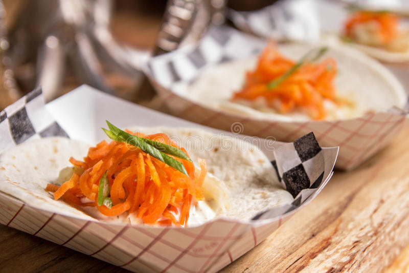 Taco som överträffas med morötter och örter arkivbilder