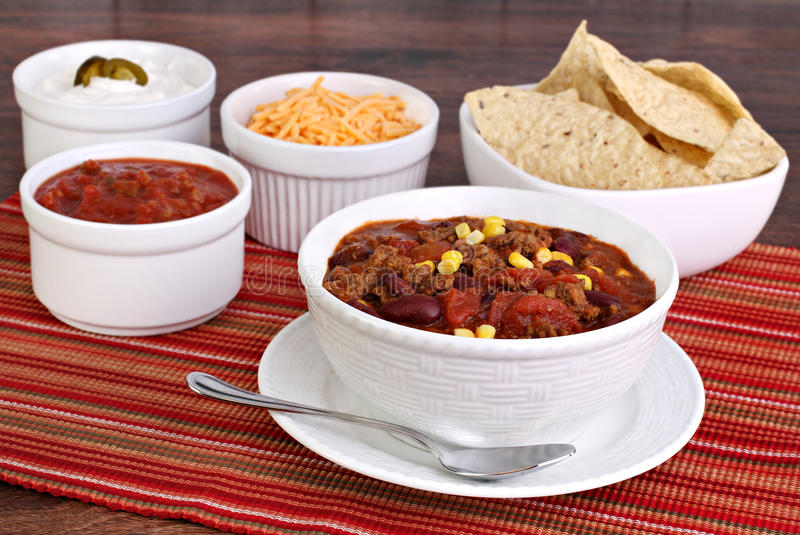 Taco Soup with assorted condiments. A bowl of taco soup surrounded with condiments including sour cream, salsa, tortilla chips and shredded cheddar cheese royalty free stock photography
