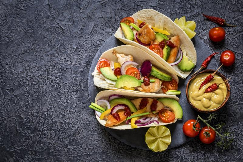 Taco; tortilla; Mexican; food; fast food; delicious; spicy; appetizing; spices; pepper; cabbage; vegetables; bread; snack; avocado royalty free stock photos