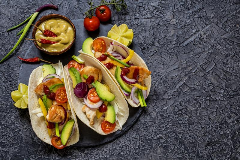 Taco; tortilla; Mexican; food; fast food; delicious; spicy; appetizing; spices; pepper; cabbage; vegetables; bread; snack; avocado royalty free stock image