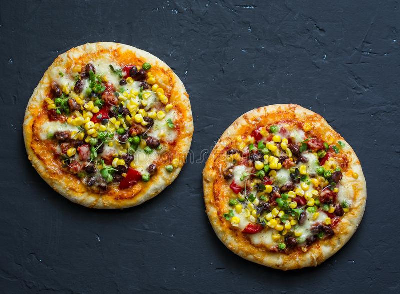 Taco vegetarian pizza. Mexican pizza with beans, corn, jalapeno pepper, mozzarella cheese on a dark background, top view. Snack, tapas stock images