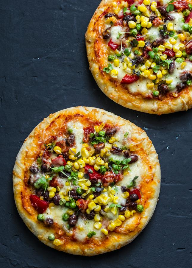 Taco vegetarian pizza. Mexican pizza with beans, corn, jalapeno pepper, mozzarella cheese on a dark background, top view. Snack, tapas royalty free stock images