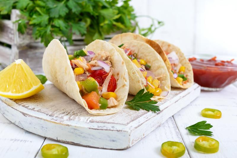 Taco - wheat tortilla with meat, vegetables, corn, greens. Delicious mexican snack on a white wooden background. royalty free stock photos